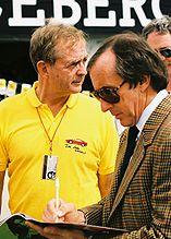 Phil Hill (polo jaune) avec Jackie Stewart lors du Grand Prix des États-Unis 1991
