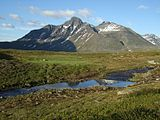 Mountain with two main peaks, composed of dark rock with traces of snow on the sides, against a bright blue sky. In the foreground, a stream cuts through grassland.