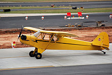 """A bright yellow, single-propeller light airplane is sitting on a paved surface at what appears to be an airport. A man is sitting in the pilot&squot;s seat, and the propeller is turning. On the tail of the plane is a logo consisting of a small bear holding a sign that says, """"Cub"""". The number on the tail rudder is N70843."""