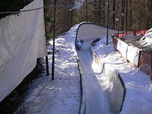 A blue sleigh in a turn of a bobsleigh run