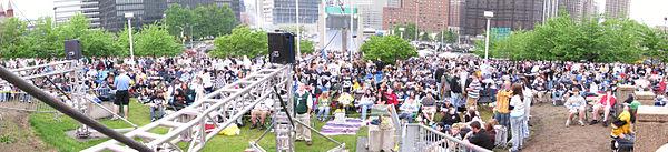 Photo panoramique d'une foule avec des immeubles en arrière plan.