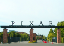 "In the foreground is a paved street leading to the gate&squot;s entrance. A sign reading ""PIXAR Animation Studios"" sits on top of stone columns in front of the gate that leads to several buildings."