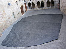 """""""Photo depicting a large copy of the Rosetta Stone filling an interior courtyard of a building in Figeac, France"""""""