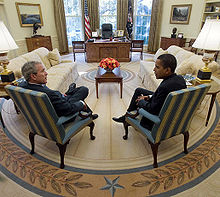 Two men sit at a distance in front of a desk with their legs crossed and their backs on an angle toward the camera. They sit at right angles to each other.