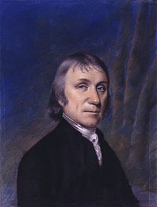 Quarter-length portrait of a man in a black coat against a purple and blue curtain backdrop.