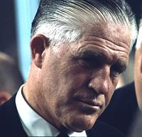 Headshot of a greying man in a suit who is indirectly facing the camera as he listens to a man a sliver of whose head is shown from the side-to-rear