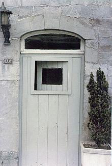 Une porte avec une petite fenêtre s'ouvrant dedans et une vitre fixe au-dessus
