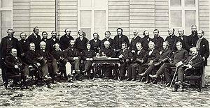 Photographie en noir et blanc d'une trentaine de participants de la Conférence de Québec en demi-cercle (la moitié sont debout, les autres, assis).