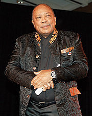 A African-American male, who has very little hair on his head and a mustache, with his hands crossed in front of him. The male is wearing a black shirt, black satin pants and a black jacket with golden colored designs.