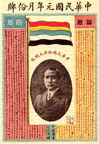 A calendar with a picture of a Chinese man in the center. On top of it stands a flag with five horizontal stripes (red, yellow, blue, white and black).