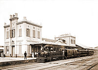 Photograph of a steam locomotive pulling passenger cars and sitting at the platform outside a large station building