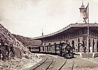 Photograph of a steam locomotive and train sitting on a curved section of track next to a curved platform and station building