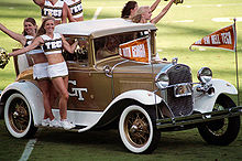 """Six women, wearing a uniform of a white skirt and a white and gold cropped top with the word """"Tech"""" on the front, ride onto the football field on the running boards and rear seat of a white-and-gold-painted antique car."""