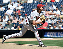 """A man in a gray baseball uniform with """"ARIZONA"""" on the chest, a red baseball cap, and a tan baseball glove on his right hand with """"50"""" on its side pitches a baseball with his left hand."""