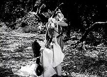A photo of two actors, Toshiro Mifune and Machiko Kyo, within a forest, in a scene from the 1950 Japanese film, Rashomon: Ms. Kyo, a young and attractive woman, is seen in an 11th Century period kimono at left of frame, kneeling at Mifune's feet; Mifune, at right of frame, wearing the rough costume of a bandit of that period, is looking down at Ms. Kyo as she appears to plead with him.