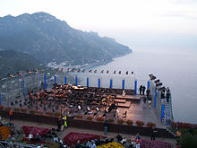 An orchestra before a performance on an outdoor stage on a balcony with water in the background.