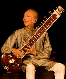An old man sits on a platform and holds a long-necked lute while looking to the side.