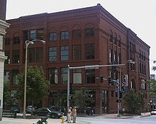 A large four-story red brick building with many windows. The building is on a street corner with the front and one of the sides visible.