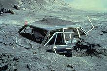 Heavily damaged car embedded in gray soil