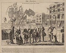 A procession of men, depicting various members of the British Parliament at the time, accompany then-Prime Minister Grenville as he carries a small coffin representing the Stamp Act near a waterfront scene with a sailing ship, cranes, bales of goods, and wharf warehouses in the background.