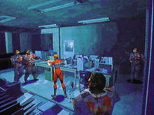 A young woman in a red and white racing suit is shooting at a pair of undead police officers, while two more enemies sneak up on her from behind. The office of the police station they are fighting in has sheets of paper scattered on the floor, and the whole scene features a bluish tint.