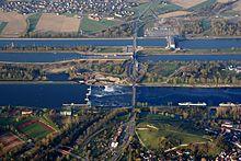 Le Rhin (au 1e plan), puis le canal séparé en 2 avec une écluse et, au fond, une centrale hydroélectrique.