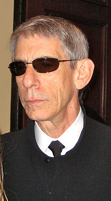 A gray-haired man with lined face and sunglasses