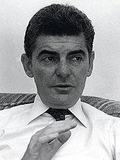 Photographie en noir et blanc de Richard Benjamin en plein discours, assis sur un canapé