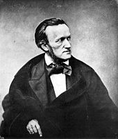 Man wearing a cloak and an outsized bow tie, facing to the right with a severe expression