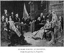 A print showing sixteen people in a large room with paintings and a large bookcase against the wall. A man with long white hair plays a grand piano as several others look on. Wagner, wearing a cap and leaning on the arm of a chair, follows the music in a score.