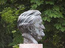 The grey sculpture of a head of a man in his sixties on a plinth with trees in the background. The front of his face is clean shaven but sideburns run under his chin.