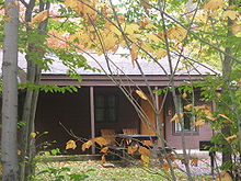 Photo of a brown clapboard-sided cabin with porch, framed by the branches and green, yellow, and orange leaves of small trees.