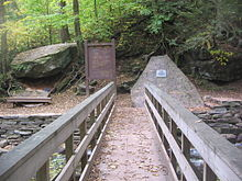 "Photo taken from a wooden footbridge with handrails over a rocky creek in a green forest. At the end of the bridge are a large boulder with a bench below it to the left, a trail sign labeled ""Waters Meet"" and ""The Falls Trail"" above a map of the trail in the center, and a natural stone monument with a metal plaque to the right."