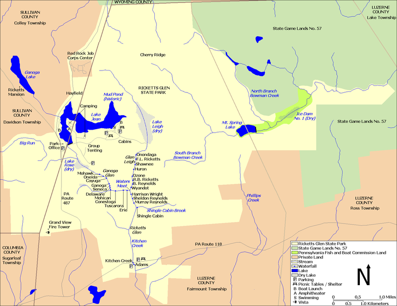 A map showing Kitchen Creek flowing southeast from Ganoga Lake, through Lake Jean, and then through the dry bed of Lake Rose into Ganoga Glen with ten waterfalls. A second branch of the creek flows south through the dry bed of Lake Leigh, then through Glen Leigh and its eight waterfalls. These branches meet at Waters Meet and the creek flows south through Ricketts Glen and its six waterfalls. The South Branch Bowman Creek is east of Lake Leigh and Big Run is west of Lake Rose. Pennsylvania Route 487 runs north-south at left, and Pennsylvania Route 118 runs east-west at the bottom of the map. County borders are also shown.
