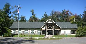 "Photo of a modern one-story building with five windows and a two-story entrance with wooden framing and ""Ricketts Glen"" in metal letters. There are trees on three sides, with a grassy lawn and parking lot in front, and a bright blue sky."