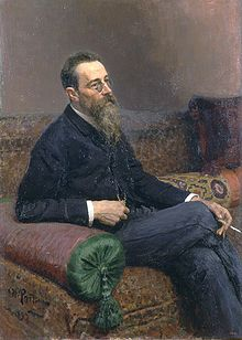 A man with glasses and a long beard sitting on a sofa, smoking