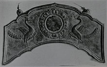 Flat metal sheet in an arc shape with embossed relief of two birds.