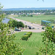 A concrete and steel structure holds a mildly busy highway crossing the river seen to the left. There are marshes and a city in the background.