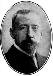 Head of a short-haired man with dark beard, looking straight to camera