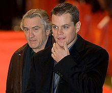 Photo of Damon and De Niro, each wearing a tuxedo jacket and a dark blue shirt.