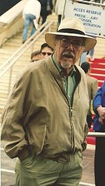 Photo of the director Robert Altman in his mid-60s, wearing a goatee, glasses, a wide-brimmed white hat and a jacket and looking directly into the camera.