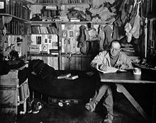 Man sitting cross-legged at table, pipe in hand, apparently writing. Much clutter of clothing, books and equipment is in the background.
