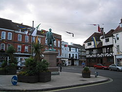 Romsey town centre, showing the statue of Palmerston on a plinth standing in the traffic island. There are one or two people in the scene (Romsey is often more crowded than this), and bunting flies from a temporary flagpole. The buildings behind the statue are three or four stories high; one of the buildings is timber-framed. Some ornamental plants are in the foreground. The sky is grey and overcast. A few parked cars are visible