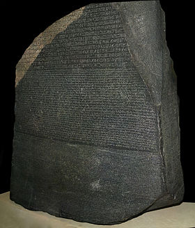 """""""A large dark grey-coloured slab of stone with text that uses Ancient Egyptian hieroglyphs, demotic and Greek script in three separate horizontal registers"""""""