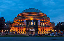 The exterior of a round building with large banners promoting the BBC Proms on a sunny day