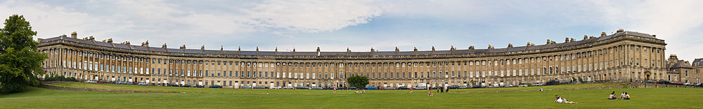Wide image of a symmetrical semicircular terrace of yellow stone buildings. Grass in the foreground.