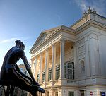 exterior of neo-classical theatre, with a statue outside of a ballerina