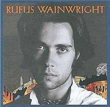 """Black and white head shot of a man; in the background is a colorful collage and the text """"Rufus Wainwright"""" appears across the top"""