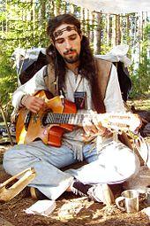 Homme habillé à la façon hippie et jouant de la guitare (photographie)