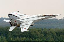 Photographie d'un MiG-25 en plein vol, au-dessus d'une forêt